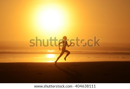 Running woman athlete silhouette at the beach of the Atlantic Ocean at sunset (full sun).