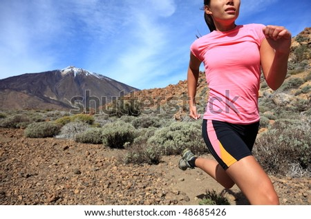 Running. Woman Cross country trail runner running on the mountain / volcano Teide on Tenerife. Beautiful mixed chinese asian / caucasian female model. - stock photo