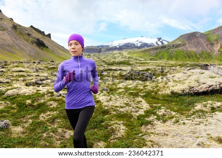 Running woman exercising - trail runner athlete. Fit female sport fitness model training jogging outdoors living healthy lifestyle in beautiful mountain nature, Snaefellsjokull, Snaefellsnes, Iceland. - stock photo