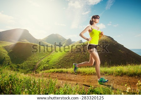 Running woman. Girl jogging on trail in mountains on field with grass in summer sunny day. Fitness. Healthy lifestyle.