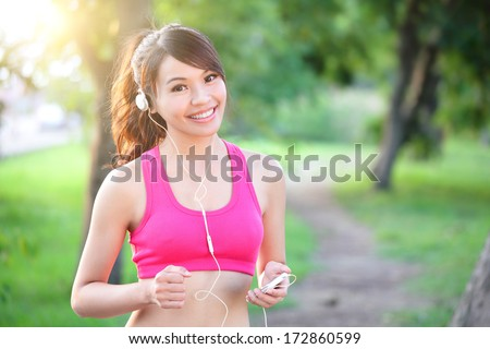 Running woman in park. Asian sport fitness model in sporty running clothes. - stock photo