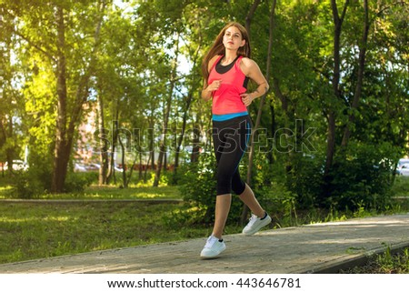Running woman in park on summer training, girl in sporty clothes. - stock photo