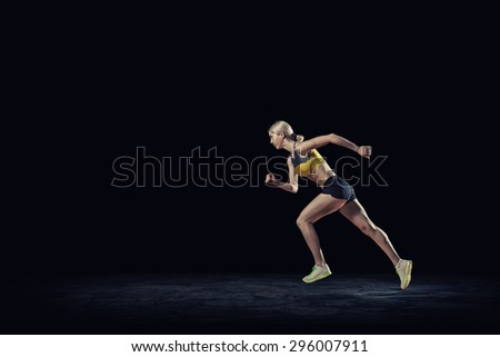 Running woman in sport wear on black background - stock photo