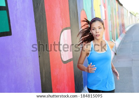Running woman jogging by Berlin Wall, Germany. Female runner training outdoors in city for marathon. Mixed race Asian Caucasian female model. - stock photo