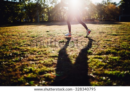 running woman  on sport yard against the sun, shadow on the grass, crop without head, big shadow on grass - stock photo