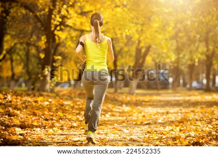 Running woman. Runner is jogging in sunny bright light in the autumn park background. Female fitness model training outside on a warm fall day and listening to music. Sport lifestyle. - stock photo