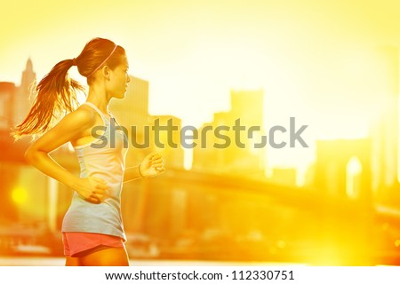Running woman. Runner jogging in sunny bright light. Female fitness model training outside in New York City with skyline and Brooklyn Bridge in background. - stock photo