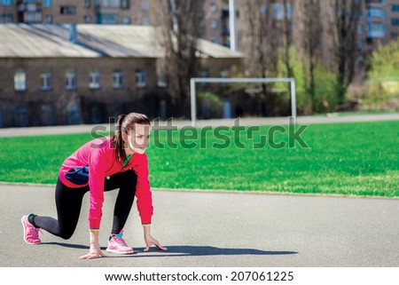 Running woman starting to run in sports clothing outdoors. Young woman at the stadium - stock photo