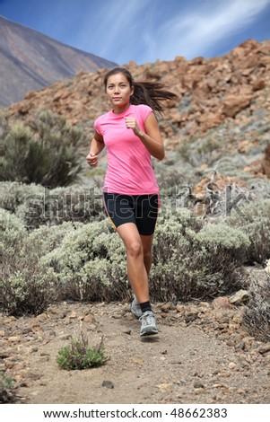 Running. Woman trail running outdoors on the volcano. Teide, Tenerife. Mixed chinese / caucasian woman model. - stock photo