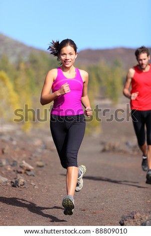 Running woman with male runner in background trail running training for marathon in volcanic landscape. Mixed race Chinese Asian / Caucasian woman jogging. - stock photo