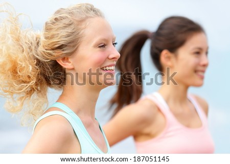 Running women runners training outdoors. Close up portrait of happy woman runner jogging outside with friends on beach. - stock photo