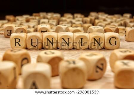 RUNNING word written on wood block - stock photo