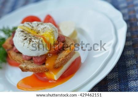 Running yolk of egg and sandwich on white plate - stock photo