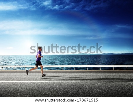 running young man and ocean in sunset time - stock photo