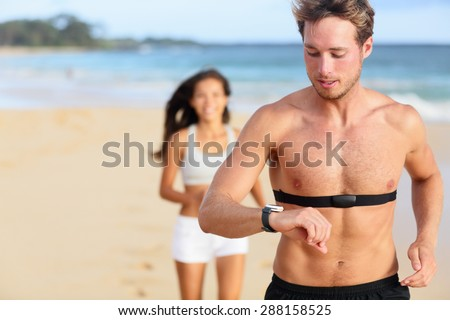 Running young man jogging on beach using heart rate monitor. Handsome shirtless male runner working out outside by the ocean wearing heart rate monitor. Closeup portrait of fit fitness athlete model. - stock photo
