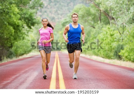 Running young multicultural couple exercising fitness outside on road in pretty nature jogging happy smiling. Asian female model and Caucasian male model training together. - stock photo