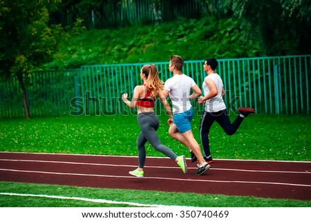 Running young people at stadium track   - stock photo