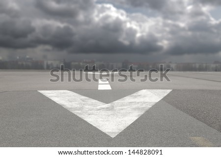 Runway airport with arrow and  storm clouds - stock photo