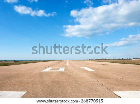 Runway, airstrip in the airport terminal with marking on blue sky with clouds background. Travel aviation concept. - stock photo