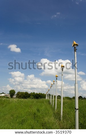 runway approach lights in field against blue sky and clouds