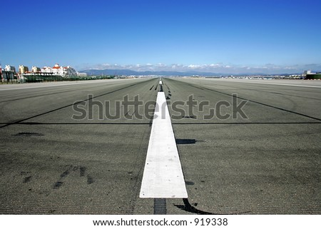 Runway at Gibraltar airport with deep rich blue sky on a sunny day - stock photo