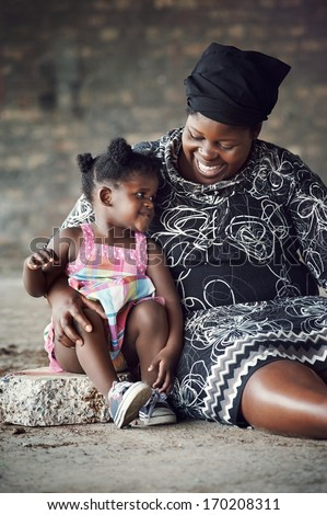 Rural African mother and baby girl smiling and having fun together - stock photo