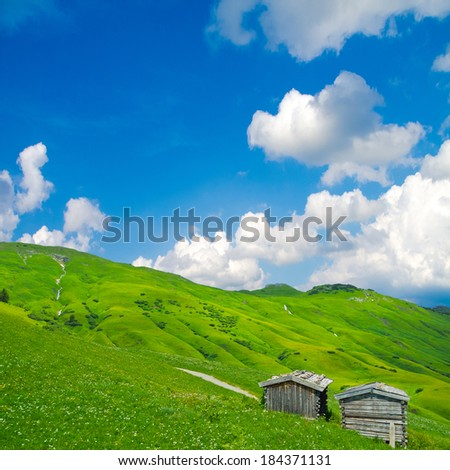 rural alpine landscape with wooden huts an beautiful sky - stock photo