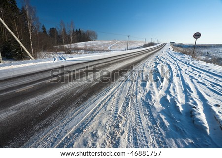 Rural asphalt road in winter with clear blue sky