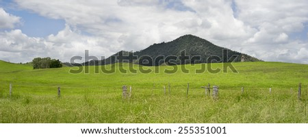 Rural Australian panorama country scene with barb wire fence line, rolling green hills, cloudy summer sky in Queensland - stock photo
