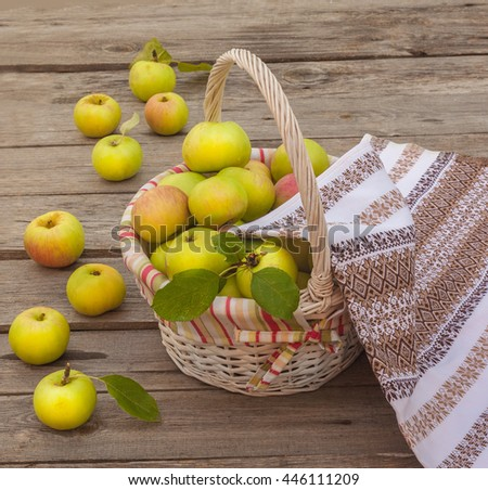 Rural autumn still life with a basket with apples  on  wooden table - stock photo