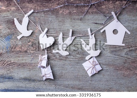 Rural background, festive decorations, decor, home decoration, heart, white, birds, wood texture background. Decor made of cardboard. Decorative toy on a rope, a sprig. Gifts bring happiness.  - stock photo