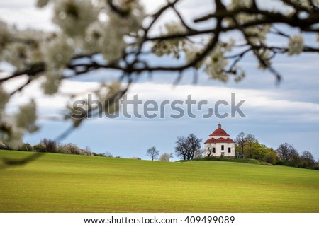 Rural baroque chapel in spring landscape - flowering tree, green field and cloudy sky. Czech Republic, Europe. - stock photo