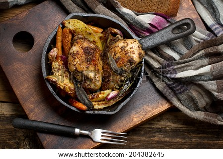 Rural chicken baked with potatoes, carrots, garlic and sage in cast iron skillet - stock photo