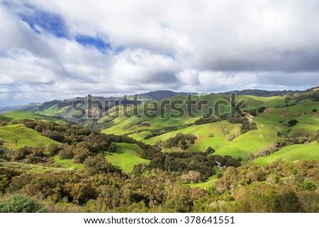 Rural coastal hills / mountains, blue sky, white clouds, & green meadows, on the Big Sur coast, California Central Coast, near Cambria CA. - stock photo