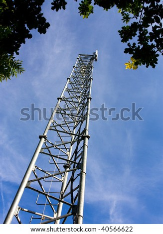 Rural communications mast from low viewpoint under tree canopy against blue sky.
