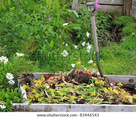 Rural compost pile with a rustic pitch fork and flowers in the background