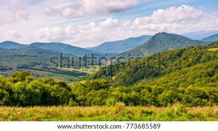 rural countryside with forested hill in mountainous area. lovely early autumn landscape with cloudy sky