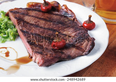 rural design new york meat style beef steak fillet on white plate with hot chili pepper served with tea cup ketchup in Gravy boat pepper mill and cutlery on napkin on wooden table - stock photo