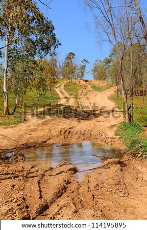 Rural dirt damaged wet road with car tire traces after heavy rain - stock photo