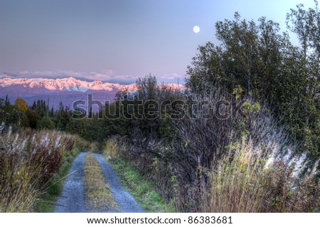 Rural dirt road at sunset with a full moon rising over snow covered mountains. - stock photo