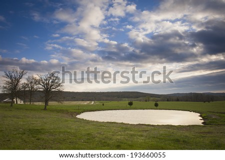 Rural farm landscape with a pond and pasture land. - stock photo