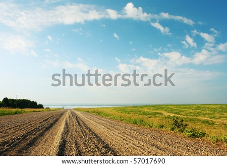 Rural gravel road and blue sky with clouds