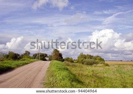Rural gravel road and house in distance. Cloudy sky and landscape of meadows. Power poles. - stock photo