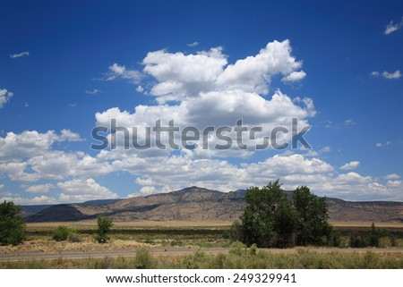Rural Highway - The American Southwest with mountains and high clouds. - stock photo
