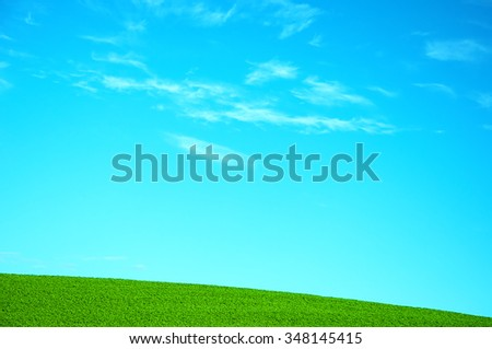 Rural hilly landscape with lush grass and bright blue sky - stock photo