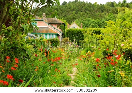 Rural house surrounded by beautiful garden. France. Vacation at countryside background. - stock photo