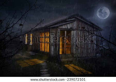 Rural house with glowing windows at night sky with moon  - stock photo