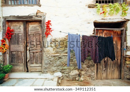Rural house with wooden doors and laundry hanging on rustic background - stock photo
