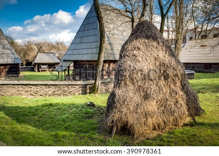 Rural image of a romanian village in eastern europe, with a hayrick in the foreground and traditional farm houses in the background - stock photo