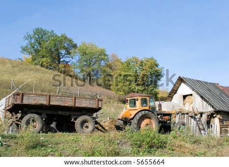 Rural landscape. An old tractor with the trailer about a shabby shed with hay. The photo is filled by mood of a rural life.